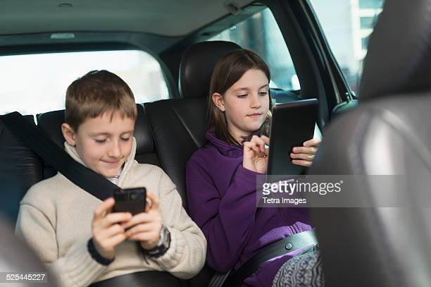USA, New Jersey, Jersey City, Boy and girl (8-9, 10-11) using digital tablet and smart phone in car