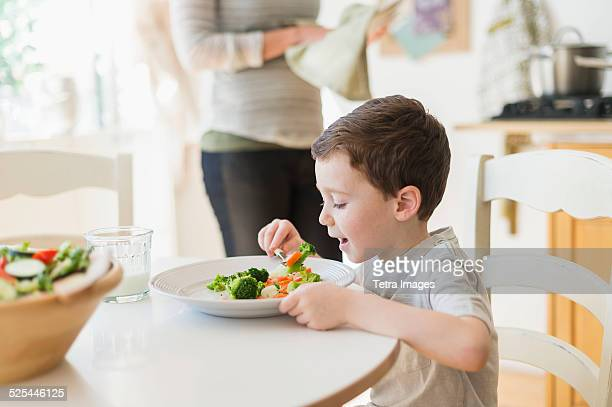 USA, New Jersey, Jersey City, Boy (6-7) eating healthy dinner, mother in background