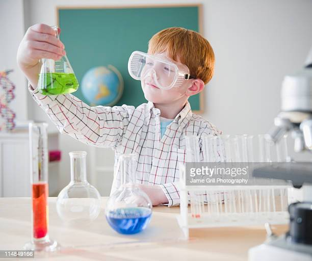 USA, New Jersey, Jersey City, Boy (8-9) holding chemical flask in science lab
