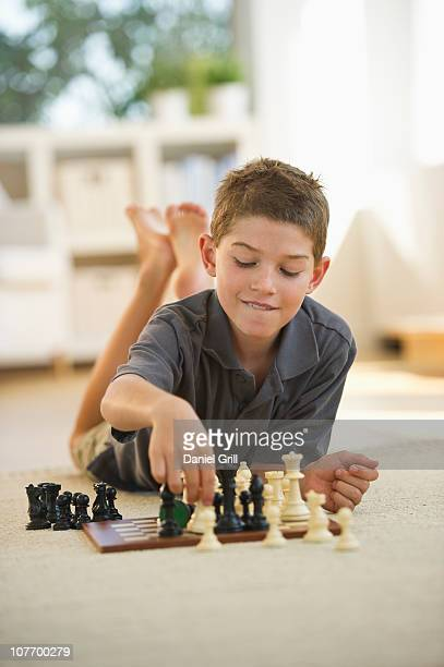 USA, New Jersey, Jersey City, Boy (10-11) lying on floor and playing chess