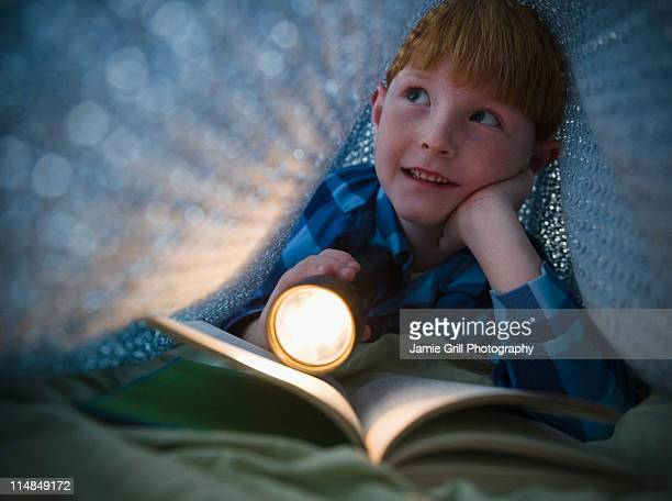 USA, New Jersey, Jersey City, Boy (8-9) reading book under bed covers