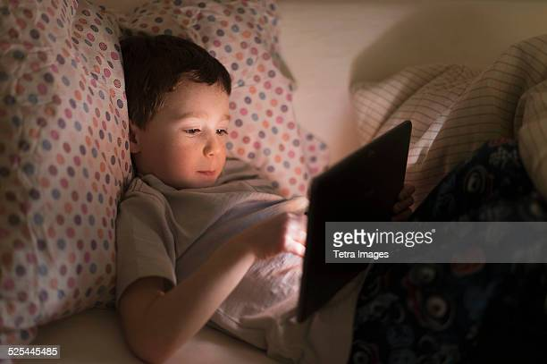 USA, New Jersey, Jersey City, Boy (6-7) using digital tablet in bed