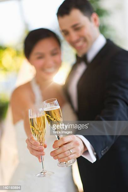 USA, New Jersey, Jersey City, Bride and groom toasting with champagne