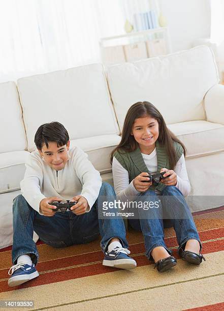 USA, New Jersey, Jersey City, Brother (12-13) and sister (10-11) playing video games