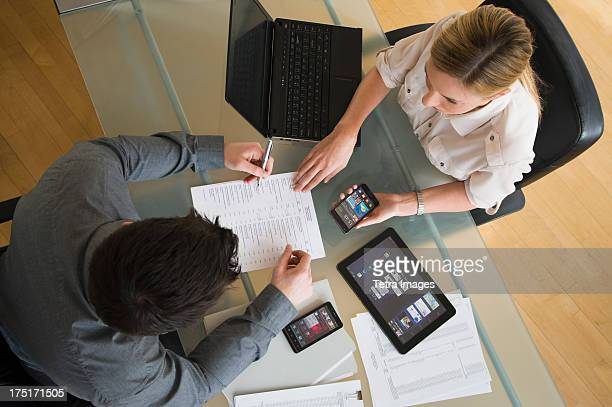 USA, New Jersey, Jersey City, Business man and woman using mobile devices