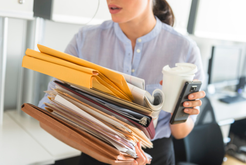 USA, New Jersey, Jersey City, Business woman holding stack of documents in office - gettyimageskorea