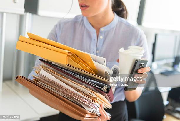 usa, new jersey, jersey city, business woman holding stack of documents in office - overworked stock pictures, royalty-free photos & images