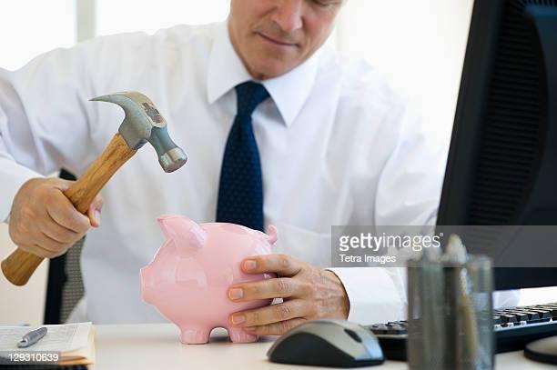 USA, New Jersey, Jersey City, Businessman hammering piggy bank