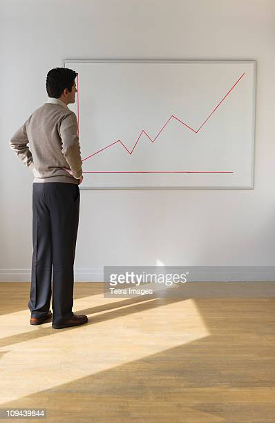 USA, New Jersey, Jersey City, Businessman observing line graph