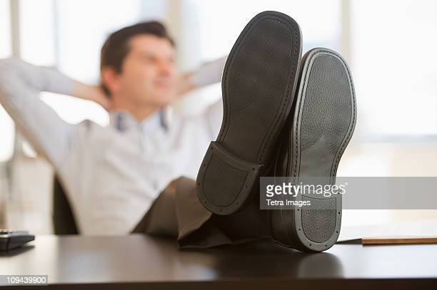 USA, New Jersey, Jersey City, Businessman with feet up on desk