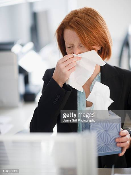 USA, New Jersey, Jersey City, businesswoman blowing nose