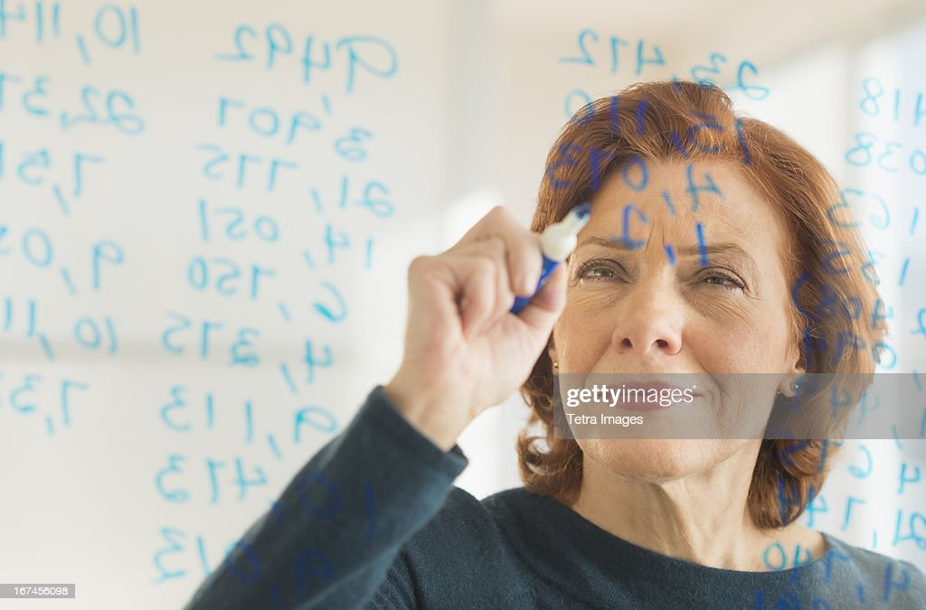 USA, New Jersey, Jersey City, Businesswoman writing on transparent board : Stock Photo