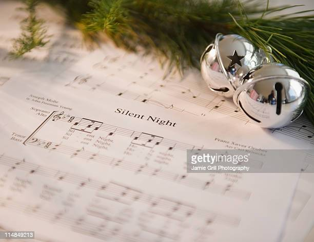 USA, New Jersey, Jersey City, Christmas baubles on carol music sheet