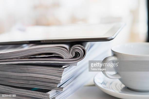 usa, new jersey, jersey city, close up of coffee cup and digital tablet on top of magazine stack - magazine stock pictures, royalty-free photos & images
