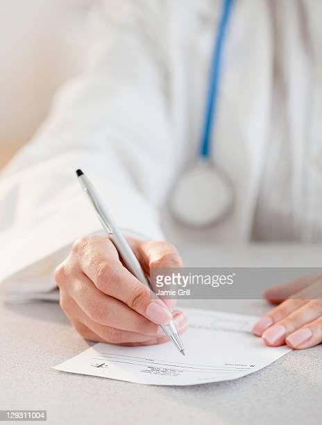 usa, new jersey, jersey city, close up of female doctor's hands writing prescription - verschreibungspflichtiges medikament stock-fotos und bilder