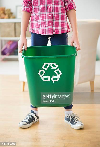 USA, New Jersey, Jersey City, Close up of girl (8-9) holding recycle bin