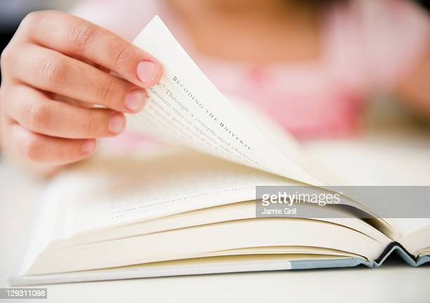 USA, New Jersey, Jersey City, Close up of girl's (8-9) hand turning pages
