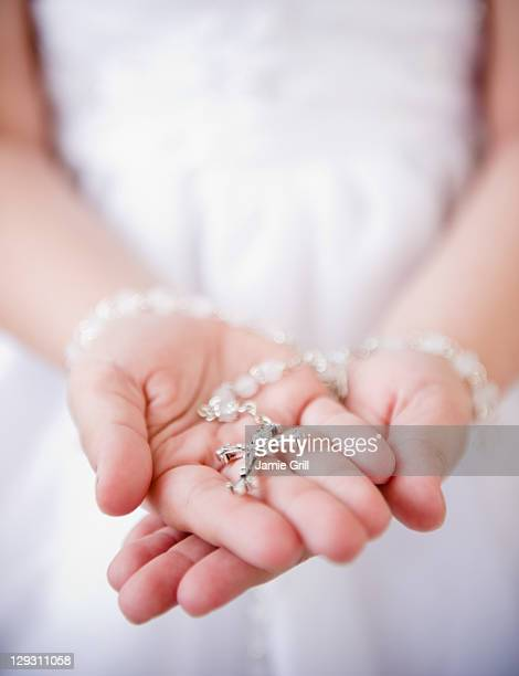 USA, New Jersey, Jersey City, Close up of girl's (8-9) hands holding rosary beads