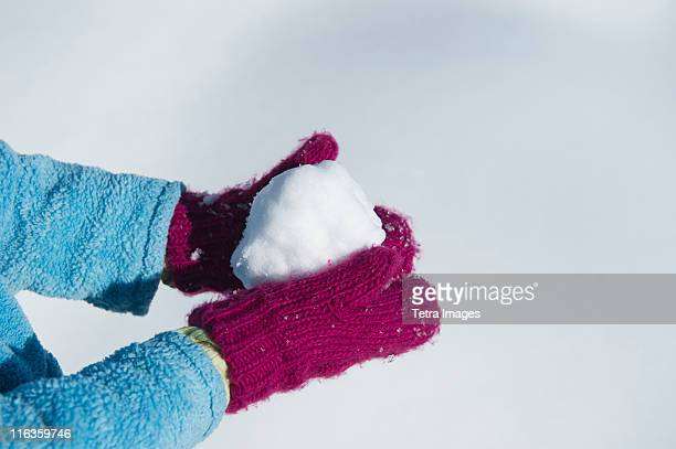 USA, New Jersey, Jersey City, close up of girl's (6-7) hands in mittens holding snowball