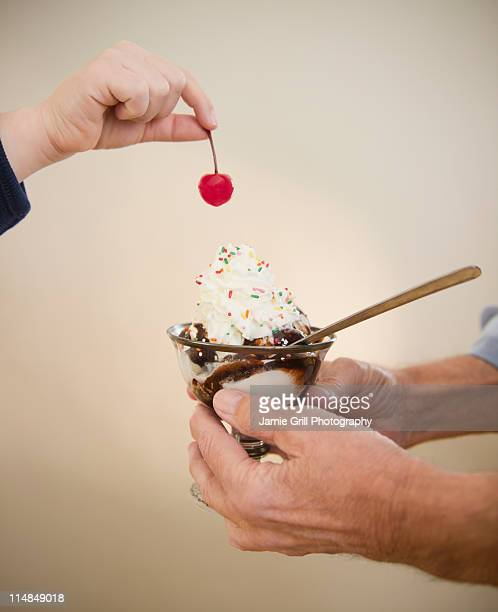 USA, New Jersey, Jersey City, close up of hands of grandfather and grandson (8-9) holding icecreame and cherry