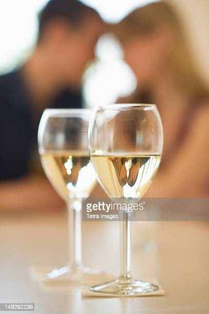 USA, New Jersey, Jersey City, Close up of wine glasses with couple in background