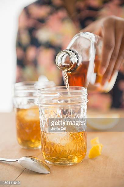 USA, New Jersey, Jersey City, Close up of woman hand pouring whiskey