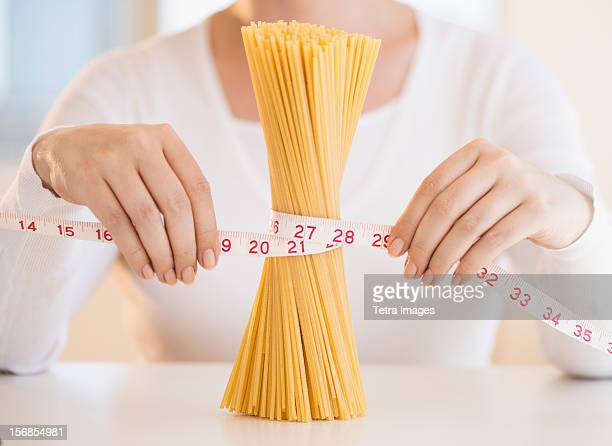 USA, New Jersey, Jersey City, Close up of woman's hands measuring pasta with tape measure