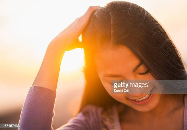 USA, New Jersey, Jersey City, Close-up of smiling teenage girl ( 16-17 years) with sunset in background