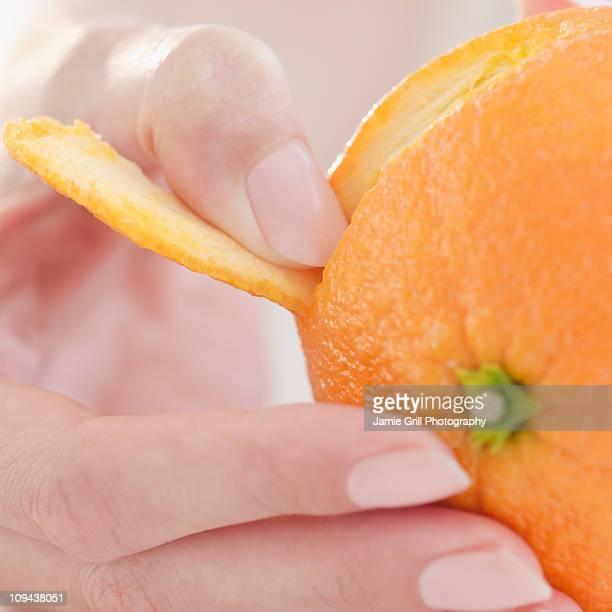 USA, New Jersey, Jersey City, Close-up view of woman's hand peeling orange