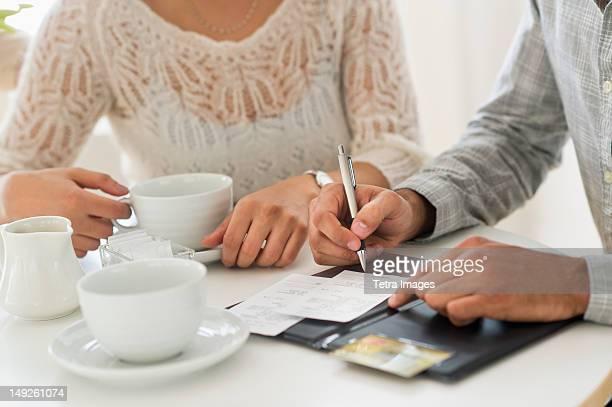 USA, New Jersey, Jersey City, Couple enjoying tea, man signing receipt