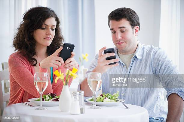 USA, New Jersey, Jersey City, Couple having dinner and text messaging