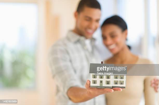 USA, New Jersey, Jersey City, Couple holding toy house