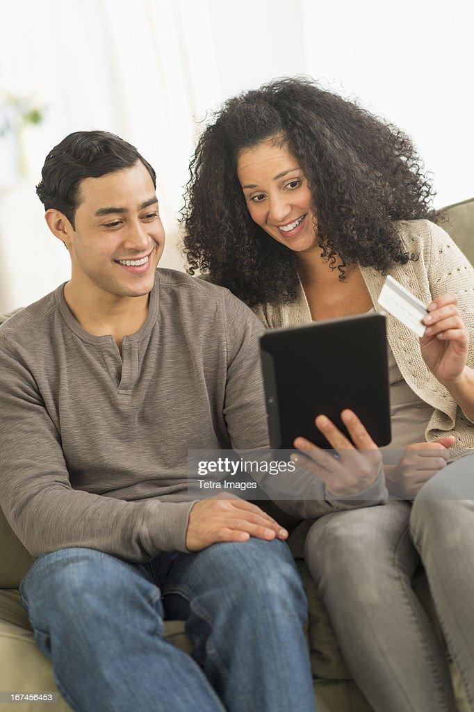 USA, New Jersey, Jersey City, Couple using digital tablet on sofa : Stock Photo