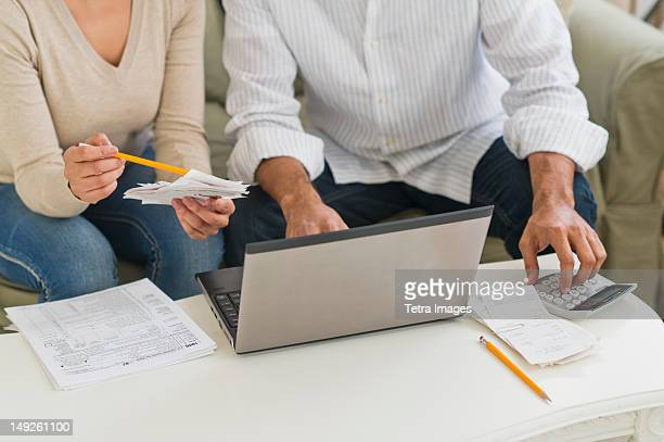 USA, New Jersey, Jersey City, Couple using laptop and calculator
