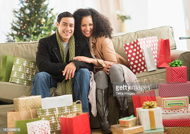 usa, new jersey, jersey city, couple with christmas presents in living room - surrounding stock pictures, royalty-free photos & images