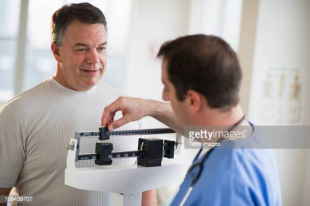 usa, new jersey, jersey city, doctor assisting male patient on weighing scales in hospital - heavy stock pictures, royalty-free photos & images