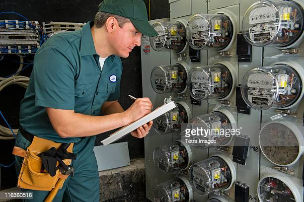 USA, New Jersey, Jersey City, electrician controlling electric meters
