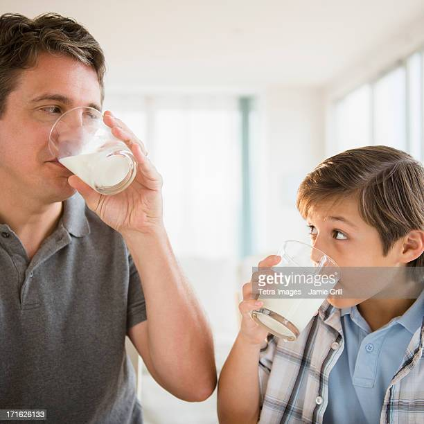 USA, New Jersey, Jersey City, Father and son (8-9) drinking milk