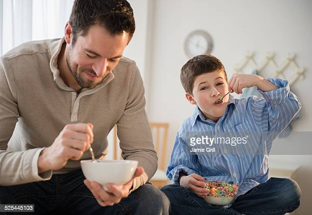 USA, New Jersey, Jersey City, Father and son (8-9) eating breakfast cereal
