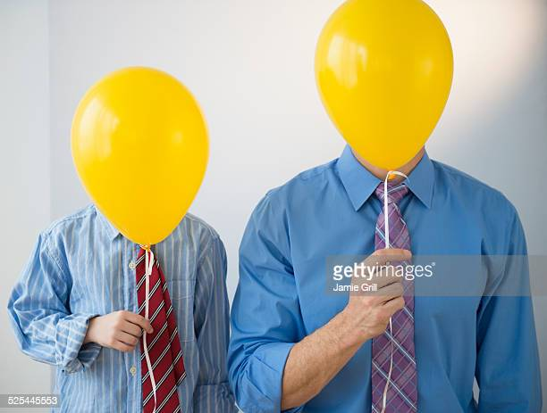 USA, New Jersey, Jersey City, Father and son (8-9) holding yellow balloons