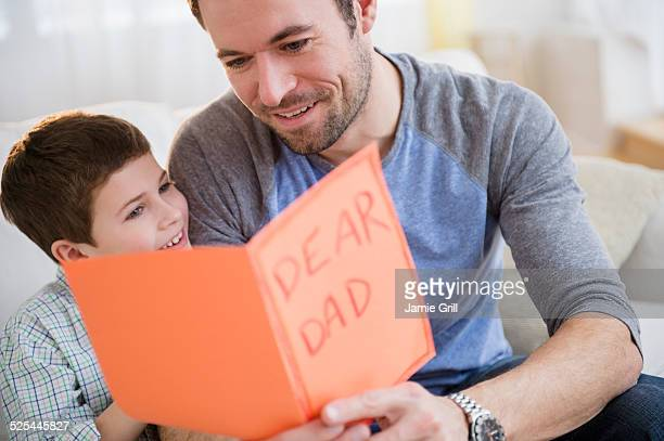 usa, new jersey, jersey city, father and son (8-9) looking at greeting card - fathers day stock pictures, royalty-free photos & images