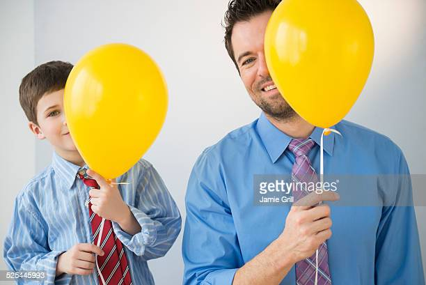 USA, New Jersey, Jersey City, Father and son (8-9) peeking behind yellow balloons