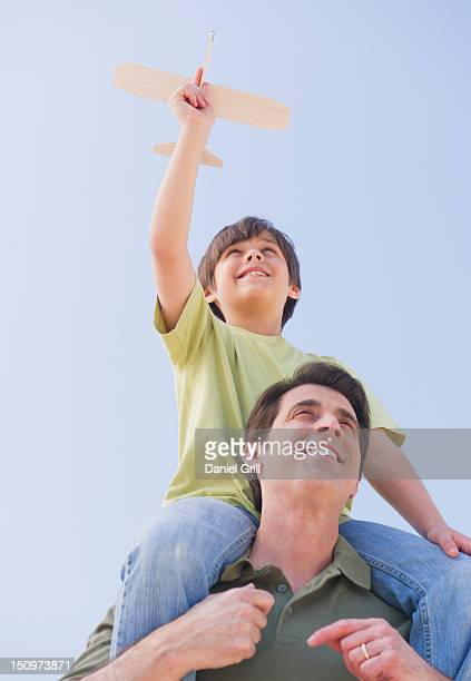 usa, new jersey, jersey city, father carrying son (10-11 years) on shoulders with model airplane - 10 11 years stock pictures, royalty-free photos & images