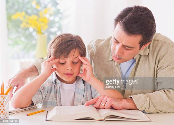 usa, new jersey, jersey city, father helping son (10-11 years) with his homework - 10 11 years stock pictures, royalty-free photos & images