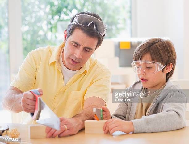 USA, New Jersey, Jersey City, Father sewing wood with son (10-11 years)