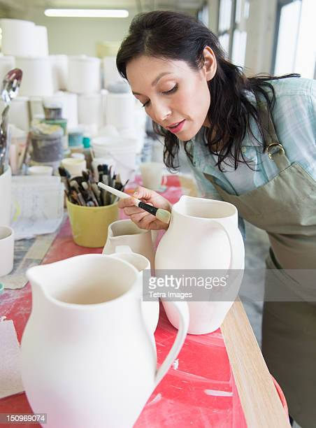 USA, New Jersey, Jersey City, Female artist decorating pottery in studio