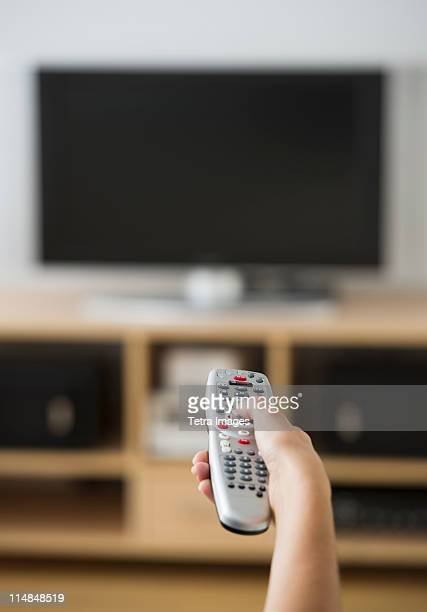 USA, New Jersey, Jersey City, Female hand holding remote control