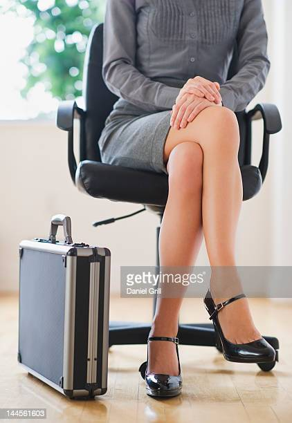 USA, New Jersey, Jersey City, front view low section of young business woman sitting in office chair with suitcase next to