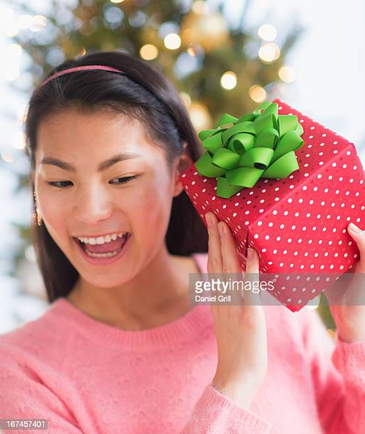USA, New Jersey, Jersey City, Front view of teenage girl ( 16-17 years) holding Christmas gift
