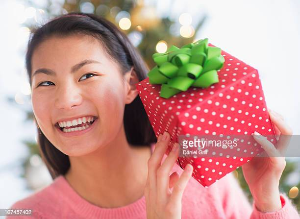 usa, new jersey, jersey city, front view of teenage girl ( 16-17 years) holding christmas gift - 16 17 years stock pictures, royalty-free photos & images